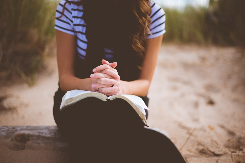 Seated woman with hands folded over bible in her lap.